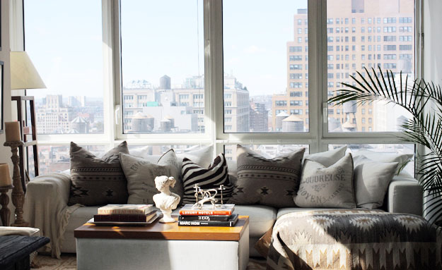 lägenhet med stora fönster soffa i vardagsrum