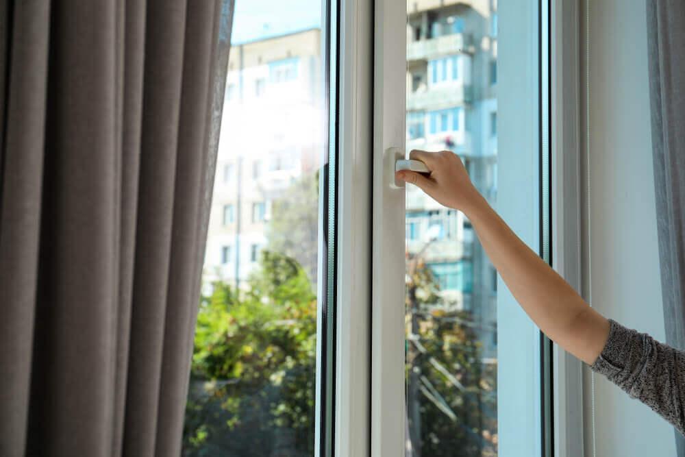 kvinna öppnar plastfönster